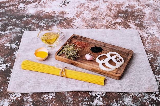 Raw spaghetti with fresh herbs on tablecloth.