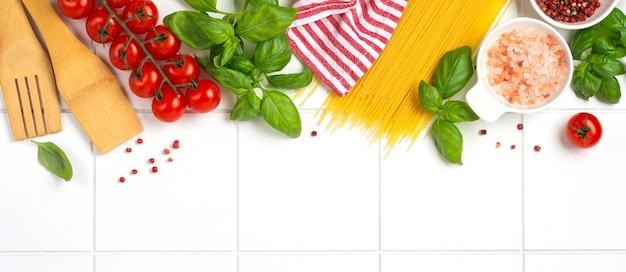 Сырые спагетти с сыром пармезан и помидорами, базиликом, чесноком и маслом на светлой стене с перцем на белой стене стола. традиционные ингредиенты для приготовления итальянской пасты. вид сверху.