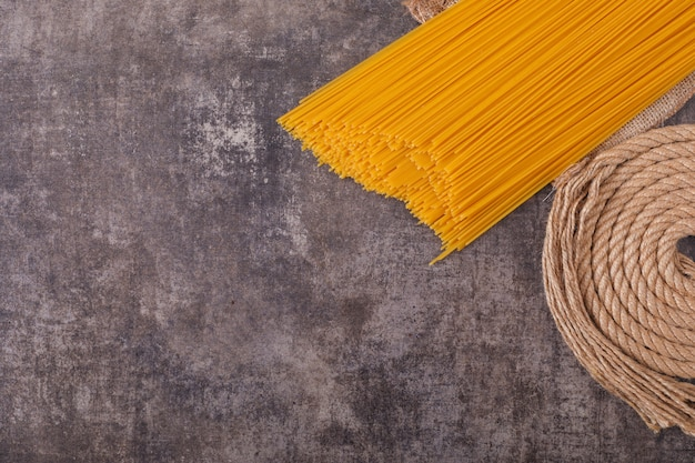 Raw spaghetti with rope top view on gray surface top view