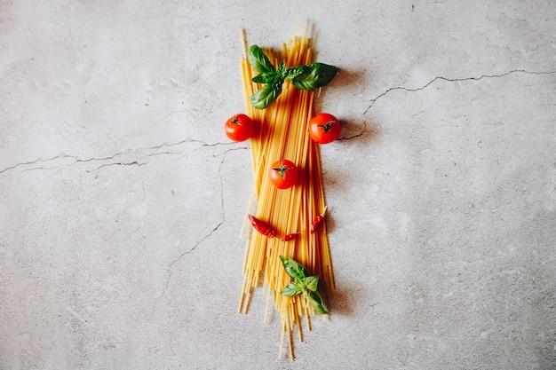 Сырые спагетти с помидорами и листьями базилика