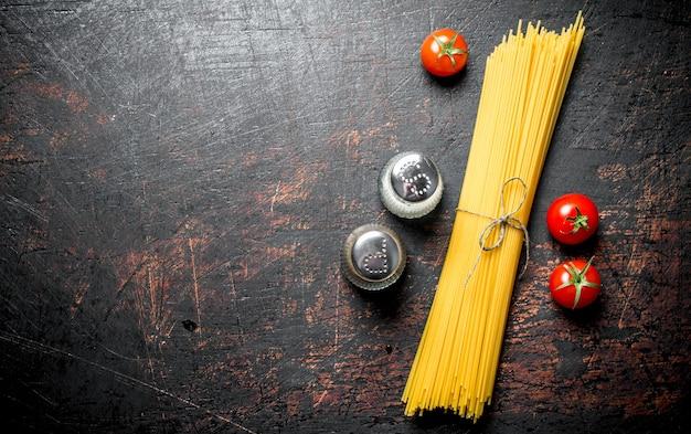Сырые спагетти с помидорами и специями. на деревенском фоне