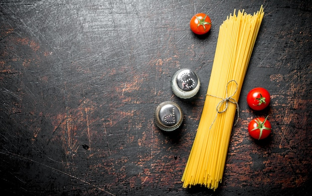 Raw spaghetti with tomatoes and spices. on rustic background