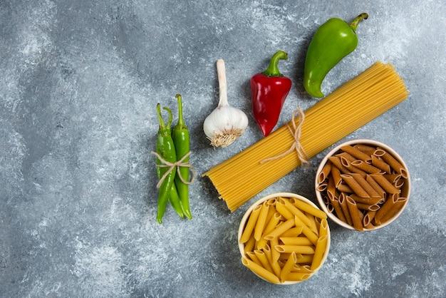 Spaghetti crudi con verdure su tavola di legno.