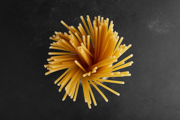 Raw spaghetties in the center on black surface.