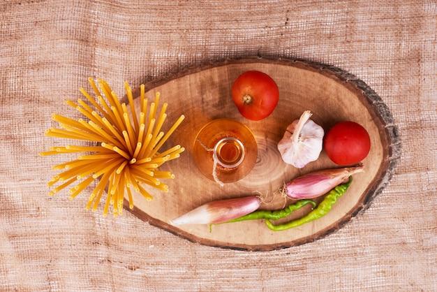 Spaghetti crudi con ingredienti su un piatto di legno, vista dall'alto.