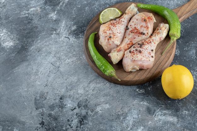 Cosce di pollo piccanti crude con pepe verde e limone.