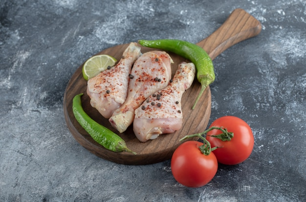 Raw spicy chicken drumsticks with green pepper and tomatoes over grey background.