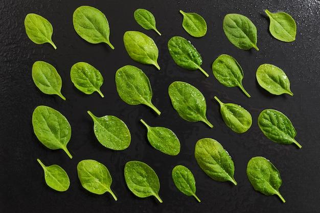黒のスレートの背景に幾何学的に配置された生のほうれん草の葉