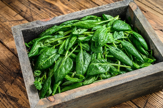 Raw spinach leaves in a wooden box.