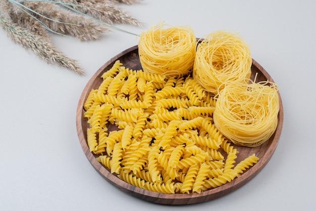 Сырые спиральные макароны и спагетти на деревянной тарелке.
