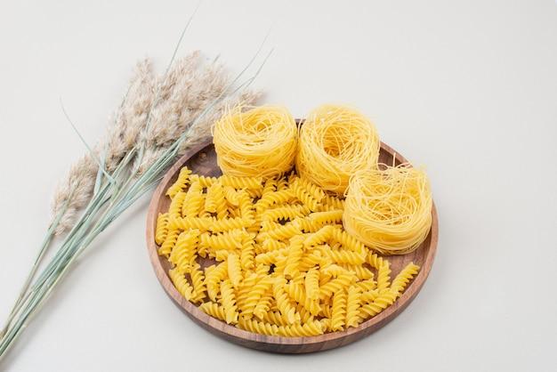 Maccheroni e spaghetti a spirale crudi sul piatto di legno con grano