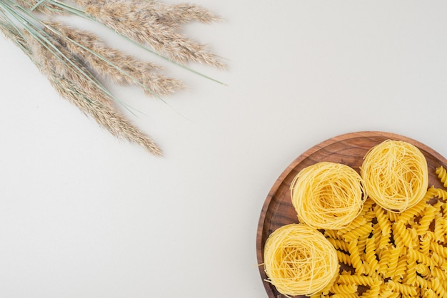 Maccheroni e spaghetti a spirale crudi sul piatto di legno