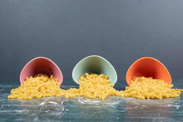 파란색 배경에 화려한 그릇에 원시 나선형 파스타. 고품질 사진