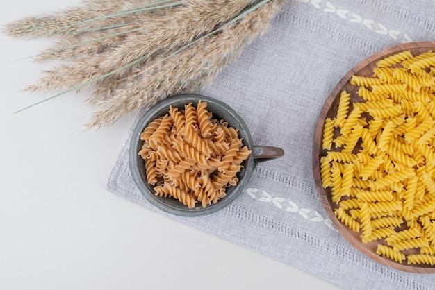 小麦とテーブルクロスのカップとプレートの生スパイラルパスタ。