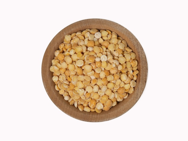 Raw split peas in wooden bowl on isolated white background