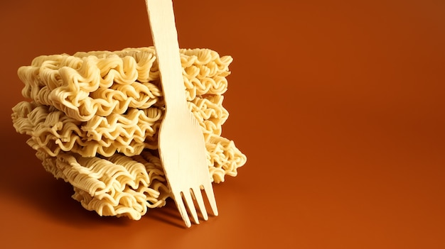 Raw square-shaped instant noodles with a wooden fork, stacked in a stack of three servings. pasta, for the preparation of which it is enough to pour boiling water and wait a few minutes. copy space.