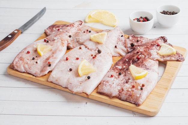 木製のまな板で調理する準備ができているスパイスとレモンの生イカの死骸。コピースペース。上面図