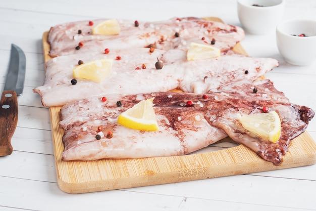 スパイスとレモンを入れた生のイカの枝肉を、木製のまな板で調理する準備ができています。スペースをコピーします。上面図