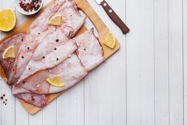 Raw squid carcass with spices and lemon ready for cooking on the table.