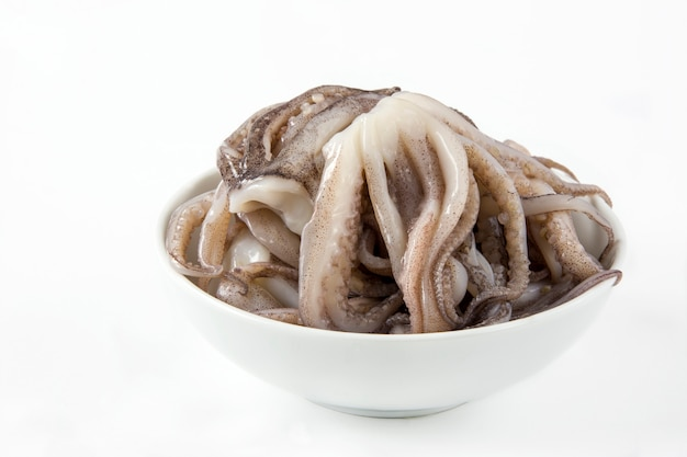 Raw squid tentacles in a bowl on white table