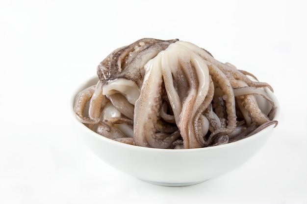Сырые кальмары щупальца в миску на белом столе
