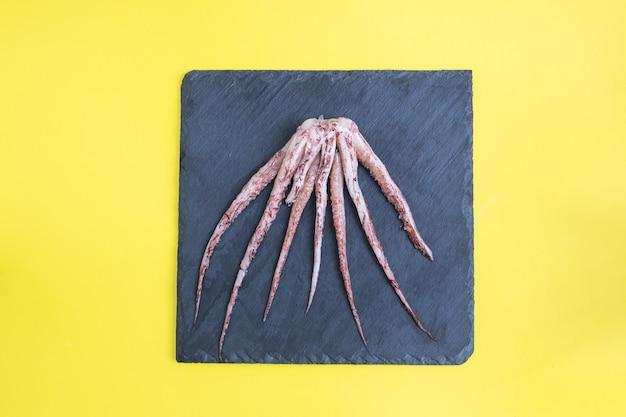 Сырые щупальца кальмаров на черной грифельной доске. копировать пространство вид сверху. желтый стол,