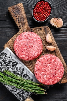 Raw steak cutlets with mince beef meat and rosemary on a wooden cutting board with meat cleaver
