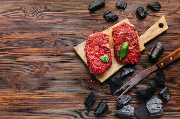 Raw steak on cutting board with coal and barbecue fork over wooden textured background