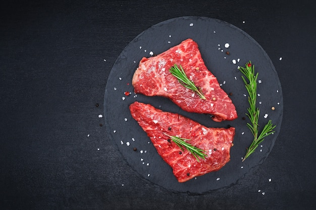 Raw steak on a cutting board with rosemary and spices
