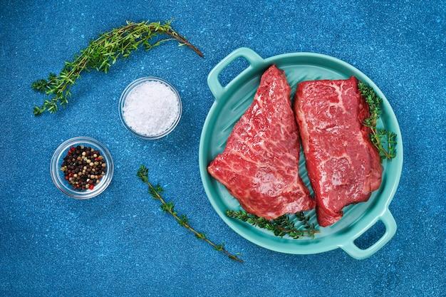まな板にローズマリーとスパイスを添えた生ステーキ