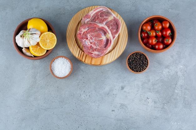Сырой стейк на деревянной разделочной доске со свежими овощами.
