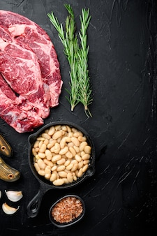 Сырой стейк, перец, зелень, чеснок, розмарин из мраморной органической говядины