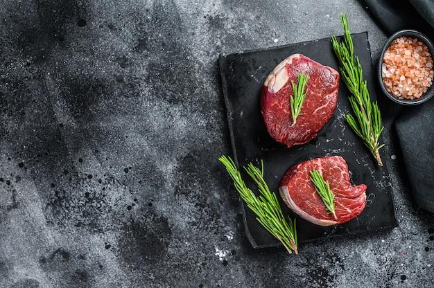 Raw steak tenderloin fillet on a stone board. black background. top view. copy space\