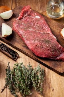 나무 테이블에 로즈마리, 소금, 후추를 넣은 생 스테이크. 고기 양념. 유기농 식품.