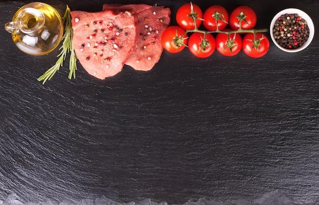 黒いスレートの表面で調理するためのスパイスと材料を使った生ステーキ