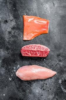 生ステーキ。ビーフトップブレード、サーモンフィレ、ターキーブレスト。有機魚、鶏肉、牛肉。黒の背景。上面図。