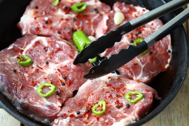 鋳鉄製グリル鍋にスパイスを入れた生ステーキクッキングステーキ