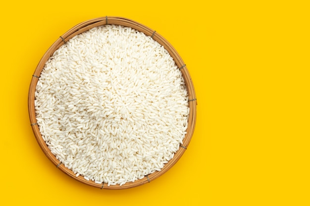 Raw sticky rice in bamboo basket on yellow background