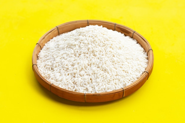 Сырой липкий рис в бамбуковой корзине на желтом фоне.