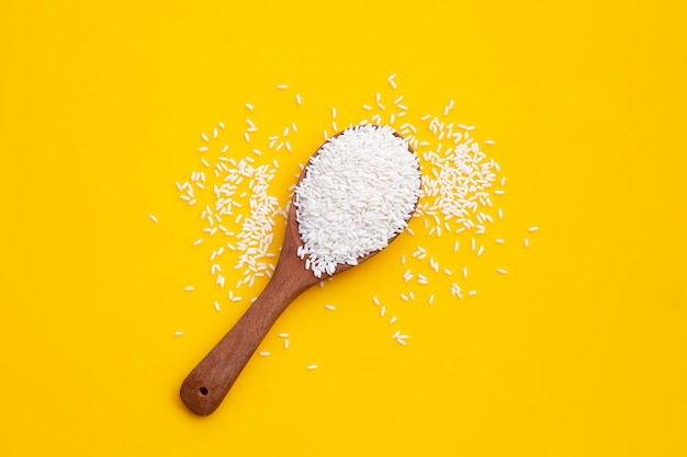 Raw sticky rice in wooden spoon on yellow background.