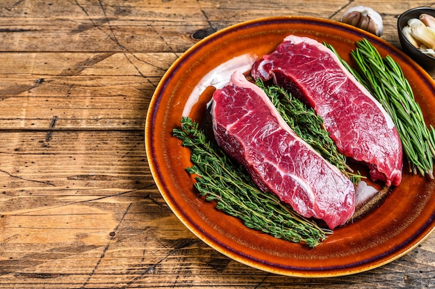 허브와 함께 접시에 원시 스트립 허리 쇠고기 고기 스테이크.