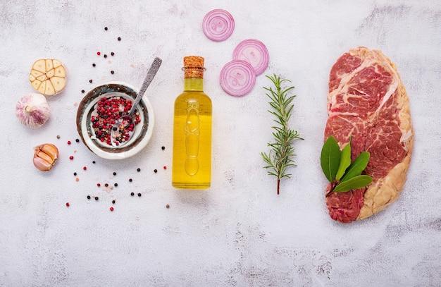 원시 striplion 스테이크는 흰색 콘크리트 배경에 설정합니다. 흰색 초라한 콘크리트 배경 꼭대기에 로즈마리와 향신료를 곁들인 신선한 생 쇠고기 스테이크의 평평한 평지.