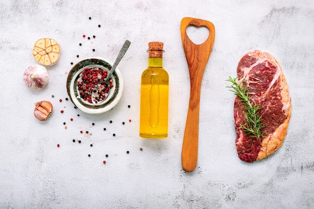 Raw striplion steak set up  on white concrete background. flat lay of fresh raw beef steak with rosemary and spice on white shabby concrete background top view.