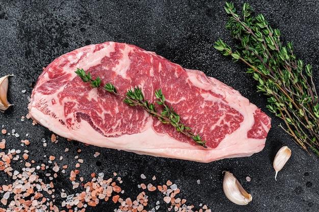 肉屋のテーブルに塩とタイムを添えた生サーロインステーキ