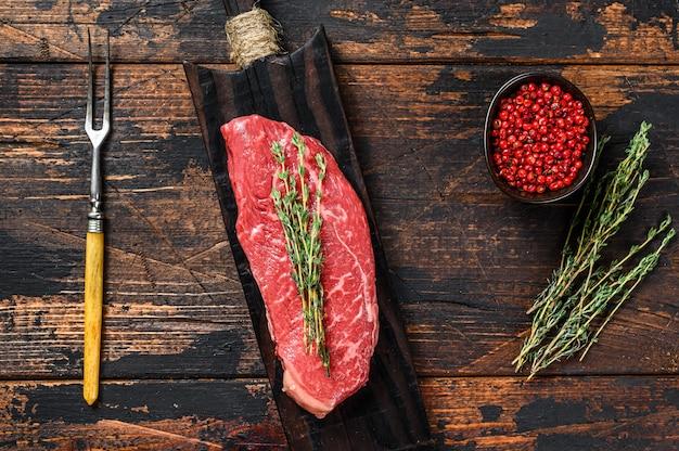 Сырой стейк стриплойн на разделочной доске, мраморная говядина. темный деревянный фон. вид сверху.