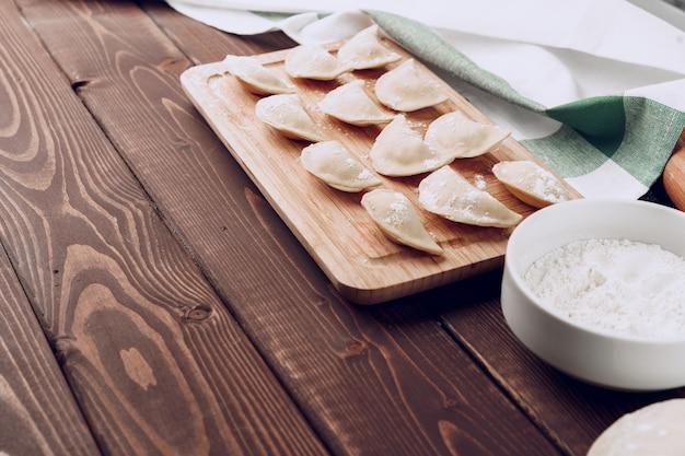 木製のまな板に生のロシアのぬいぐるみ餃子