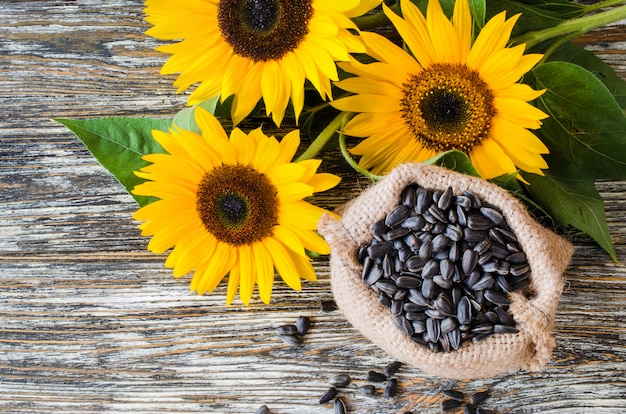 Raw sunflower seeds in burlap bag on a wooden table