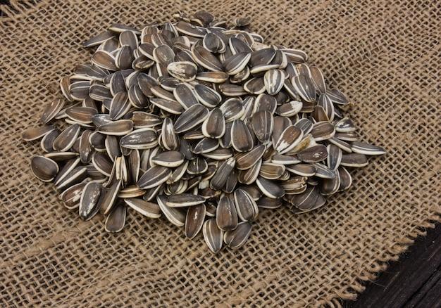 Сырцовые семена подсолнуха в мешочке из ткани на деревянном столе на фоне и желтый солнцецвет. жареные зерна подсолнуха в экологической упаковке.