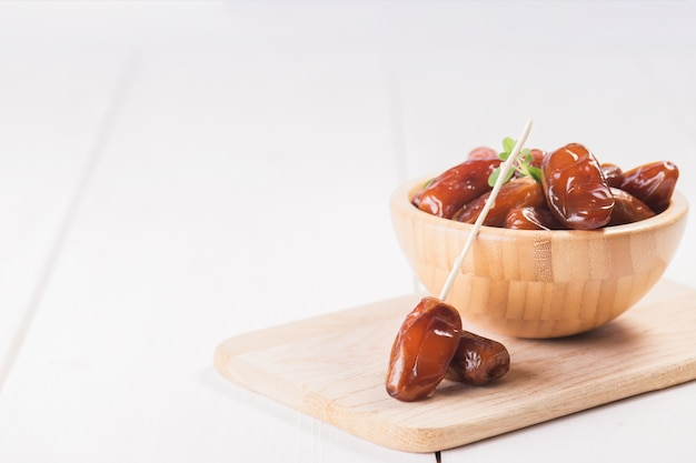 Raw sweet dry dates in a wooden bowl