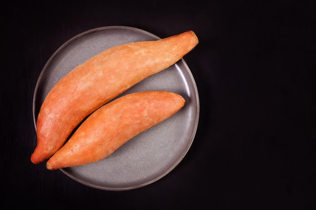 Raw sweet potatoes on the black surface. top view.